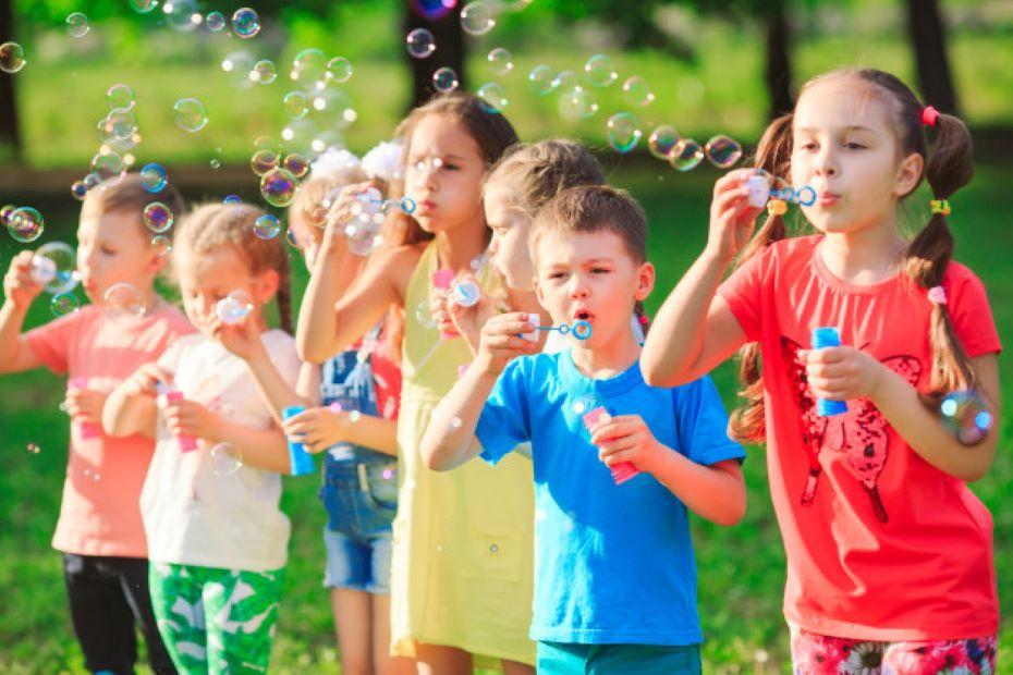 group children blowing soap bubbles